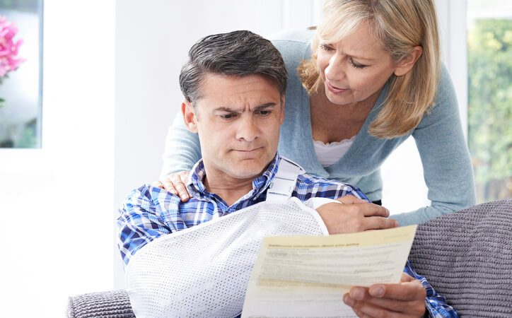 Man in bandage looking at psychological report with wife